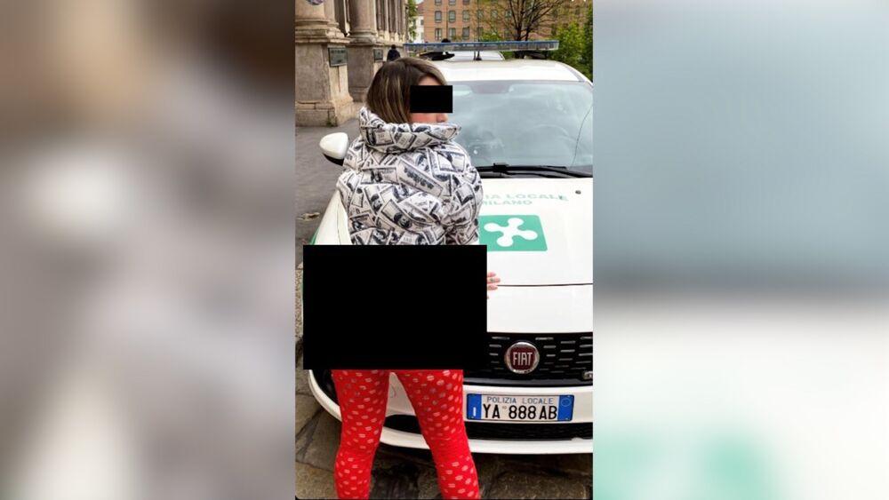 La ragazza che posa sull'auto della Locale (davanti al comando) con il 'lato B' di fuori