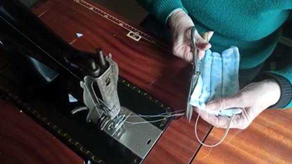 Coronavirus, mamma e figlio milanesi fanno le mascherine in casa con una vecchia macchina da cucire